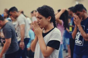 Does prayer work? Woman earnestly praying in church