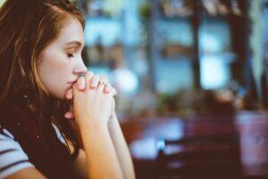 girl praying structured prayer in church