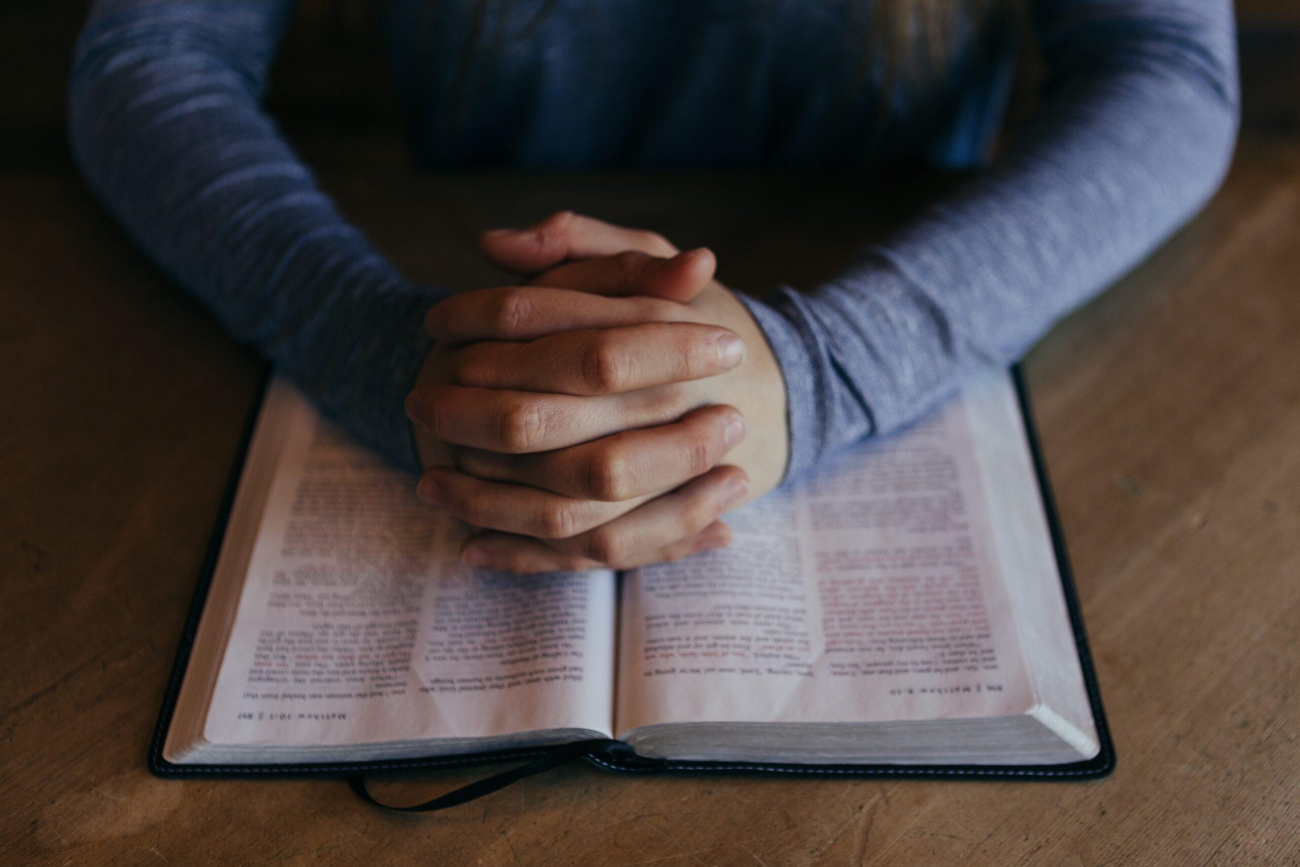 man praying using prayer structure over Bible