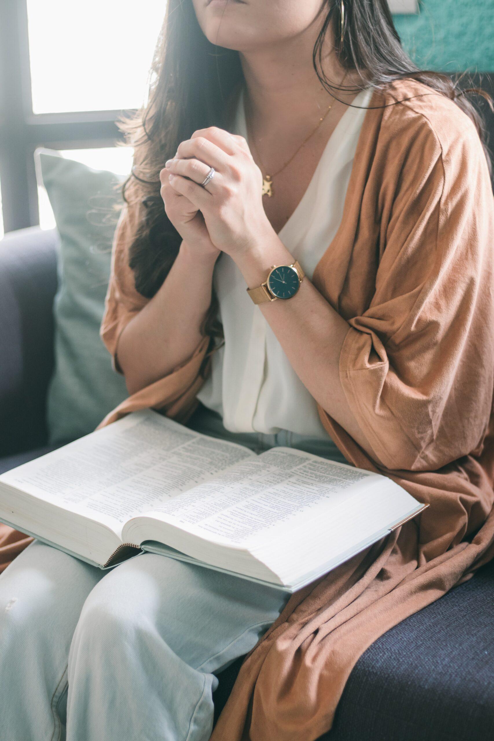 woman praying with Bible in lap