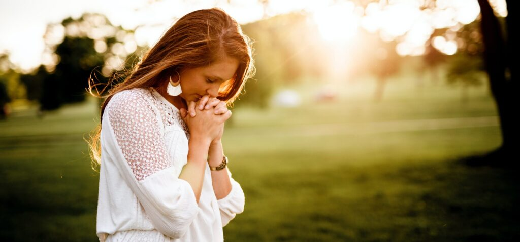 woman praying using structure of prayer in field